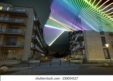 light beam passing through a residential / apartment building. It is evening / night and the colored light beams are clearly visible - buildings are Scandinavian / Copenhagen