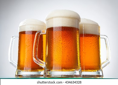 Light beer with foam in a circle on white background with barley and malt