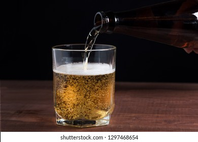 light beer in a glass on a wooden table