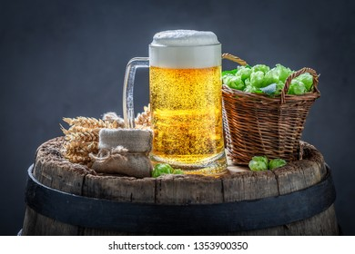 Light beer with hops and wheat on old wooden barrel