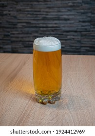 Light beer in a transparent glass glass with foam on the table
