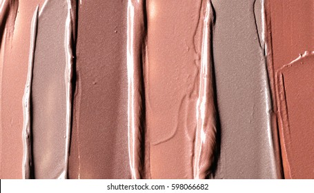 Light beige and brown makeup smears of creamy foundation background. Light beige and brown creamy foundation texture background