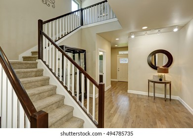 Light beige hallway interior. Carpeted staircase, hardwood floor, console table with mirror and entrance door on the background. Northwest, USA