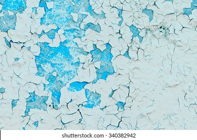 Light beige and turquoise peeling paint on the old rough concrete surface - textured background