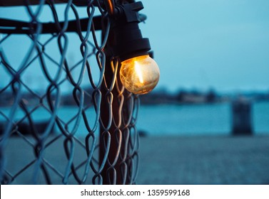 Light blub hanging on fence