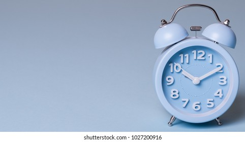Light blue alarm clock against pastel color background