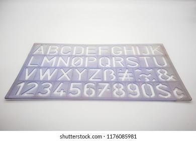 Light blue alphabet stencil lettering PVC plastic ruler template isolated on white background