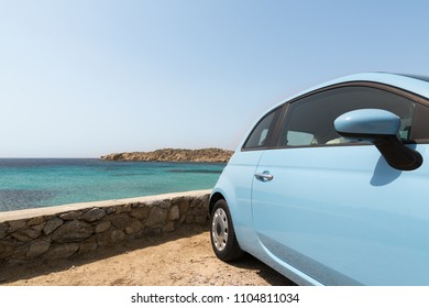 Light blue car parked next to the sea in Mykonos island, greece. Wide angle lens shot, close-up space for text.