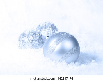 Light blue Christmas ornaments in a bed of white snow. Selective focus on band of glitter on large ornament.