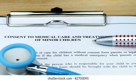 A light blue colored stethoscope on a metal clipboard along with a pen for you to sign a  medical consent form for a minor.