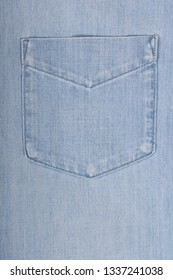 Light blue denim shirt pocket in close up shot,  fabric texture background with copy space, flat lay