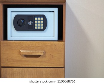 A light blue digital fireproof rectangle safe box in the brow wooden cabinet  beside the white wall