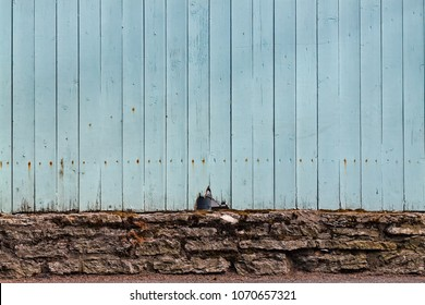 A light blue fence has a crack on a street in Tallinn, Estonia. The brick foundations and the blue color are very typical in the capital of Estonia.