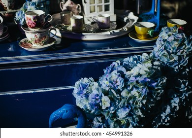 Light blue flowers stand on a blue flamigo figure behind a blue piano covered with tea services