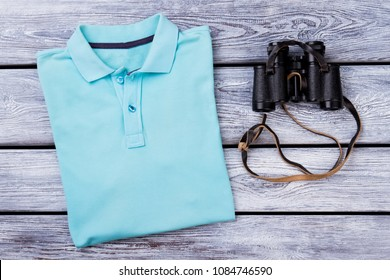 Light blue folded polo t shirt and binoculars. Top view. Wooden desk surface background.