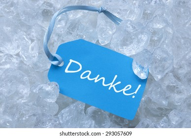 Light Blue Label With Blue Ribbon On White Transparent Crushed Ice Cubes As Background. German Text Danke Means Thank You For Cool Greetings.Close Up Or Macro View.