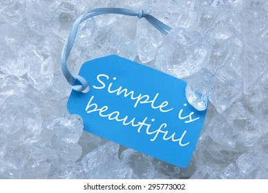 Light Blue Label With Blue Ribbon On White Transparent Curshed Ice Cubes As Background. English Quote Simple Is Beautiful For Cool Greetings.Close Up Or Macro View.