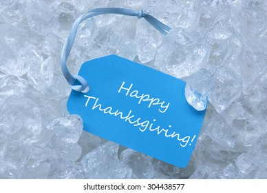 Light Blue Label With Blue Ribbon On White Transparent Curshed Ice Cubes As Background. English Text Happy Thanksgiving For Cool Greetings.Close Up Or Macro View.