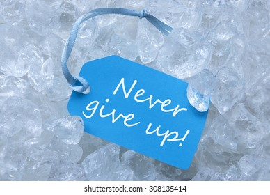 Light Blue Label With Blue Ribbon On White Transparent Curshed Ice Cubes As Background. English Quote Never Give Up For Cool Greetings.Close Up Or Macro View.