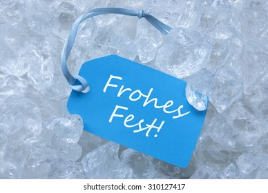 Light Blue Label With Blue Ribbon On White Transparent Curshed Ice Cubes As Background. German Text Frohes Fest Means Merry Christmas For Cool Greetings.Close Up Or Macro View.