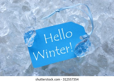 Light Blue Label With Blue Ribbon On White Transparent Curshed Ice Cubes As Background. English Text Hello Winter For Cool Greetings.Close Up Or Macro View.