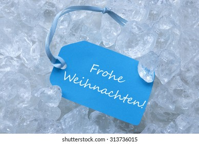 Light Blue Label With Blue Ribbon On White Transparent Curshed Ice Cubes As Background. German Text Frohe Weihnachten Means Merry Christmas For Cool Greetings.Close Up Or Macro View.