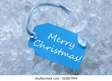 Light Blue Label With Blue Ribbon On White Transparent Curshed Ice Cubes As Background. English Text Merry Christmas For Cool Greetings.Close Up Or Macro View.