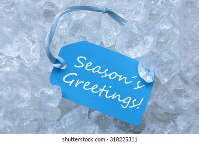 Light Blue Label With Blue Ribbon On White Transparent Curshed Ice Cubes As Background. English Text Seasons Greetings For Cool Greetings.Close Up Or Macro View.