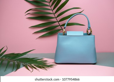 Light blue leather female bag on the pink background in the studio. There are green branches next to it. Closeup. Horizontal.
