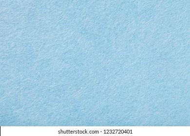 Light blue matte background of suede fabric, closeup. Velvet texture of seamless sky woolen felt.