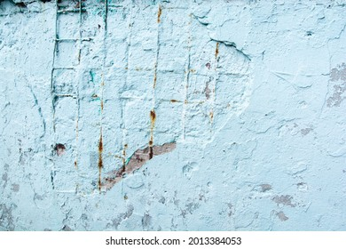 light blue painted aged concrete surface with cracks and visible rusty reinforcement