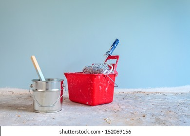 Light blue painted wall with painting tools in front on a concrete floor