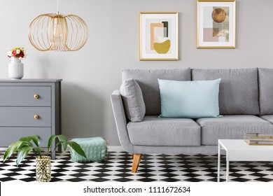 Light blue pillow placed on grey couch in bright living room interior with checkerboard linoleum floor, fresh flowers in vase on cupboard, two posters hanging on the wall and gold lamp