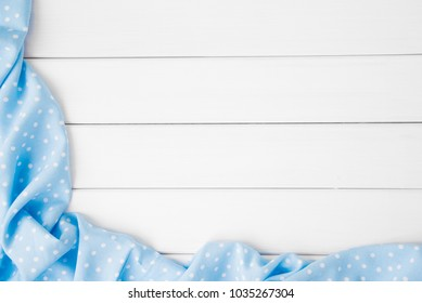 Light blue polka dots folded tablecloth over bleached wooden table. Top view image. Copyspace for your text