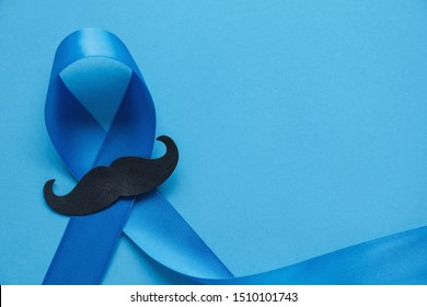 Light blue ribbon with mustache on blue background , Prostate Cancer Awareness, Movember Men health awareness, November Blue, International Men's Day