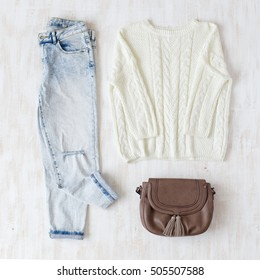 Light blue ripped boyfriend jeans, white oversize knitted sweater and small brown leather bag with tassels on white wooden background. Overhead view of woman's casual day outfits. Trendy hipster look.