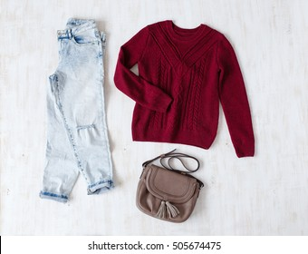 Light blue ripped boyfriend jeans, red oversize knitted sweater and small brown leather bag with tassels on white wooden background. Overhead view of woman's casual day outfits. Trendy hipster look.