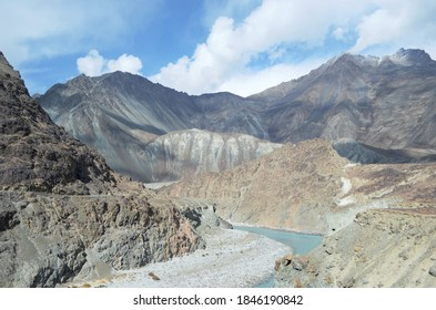 A light blue river runs through a valley bordered by rocky mountain slopes in Ladahk, India. The slopes are patterned with mineral deposits. A road is just visible. The sky is blue with white clouds.