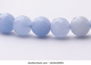 Light blue rounded beads on a string, jewelry craft concept background. Extreme close up beaded necklace, on bright gray background. Blue candy died jade beads, semi precious stone jewelry material.