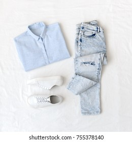 Light blue shirt, ripped boyfriend jeans and white lace up sneakers lying on white sheet. Overhead view of woman's casual day outfit. Trendy hipster look. Flat lay, top view. Basic everyday clothes.