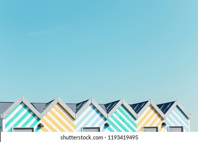 Light blue sky background and top roofs of colourful striped beach huts and copy space above