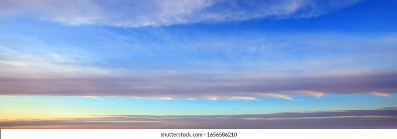 Light blue spring sky background with long striped clouds on the horizon.