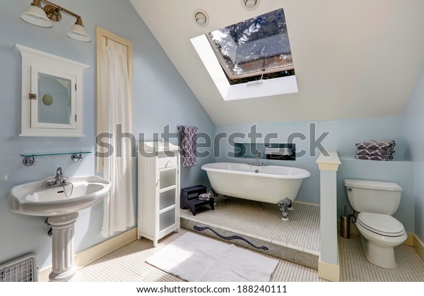 Light blue velux bathroom with window. View of white antique freestanding bath tub, washbasin stand and toilet