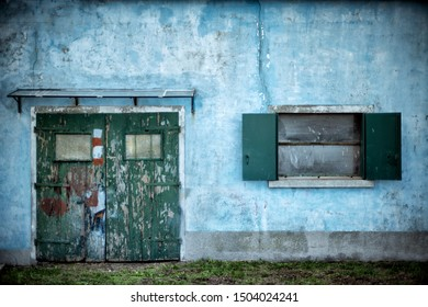 Light blue wall with green shuttered door and an open window