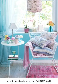 light blue wall and home corner with white table and chair with home decoration pillow blanket frame and lamp concept vase of flower in the window and pink carpet style