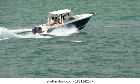 Light blue and white motor boat powered by two outboard engines speeding on the Florida Intra-Coastal Waterway .