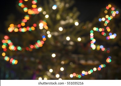 Light blurred multicolored lights on a real Christmas tree outside in the snow. Bokeh.