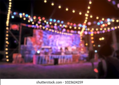 Light bokeh of people sitting in front of the stage at outdoor concert event.