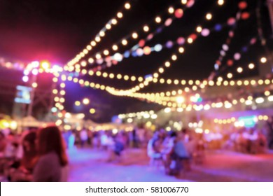 Light bokeh of people sitting at outdoor concert event.