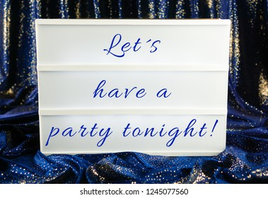 Light box with the words let´s have a party tonight, blue and sparkling curtain in the background